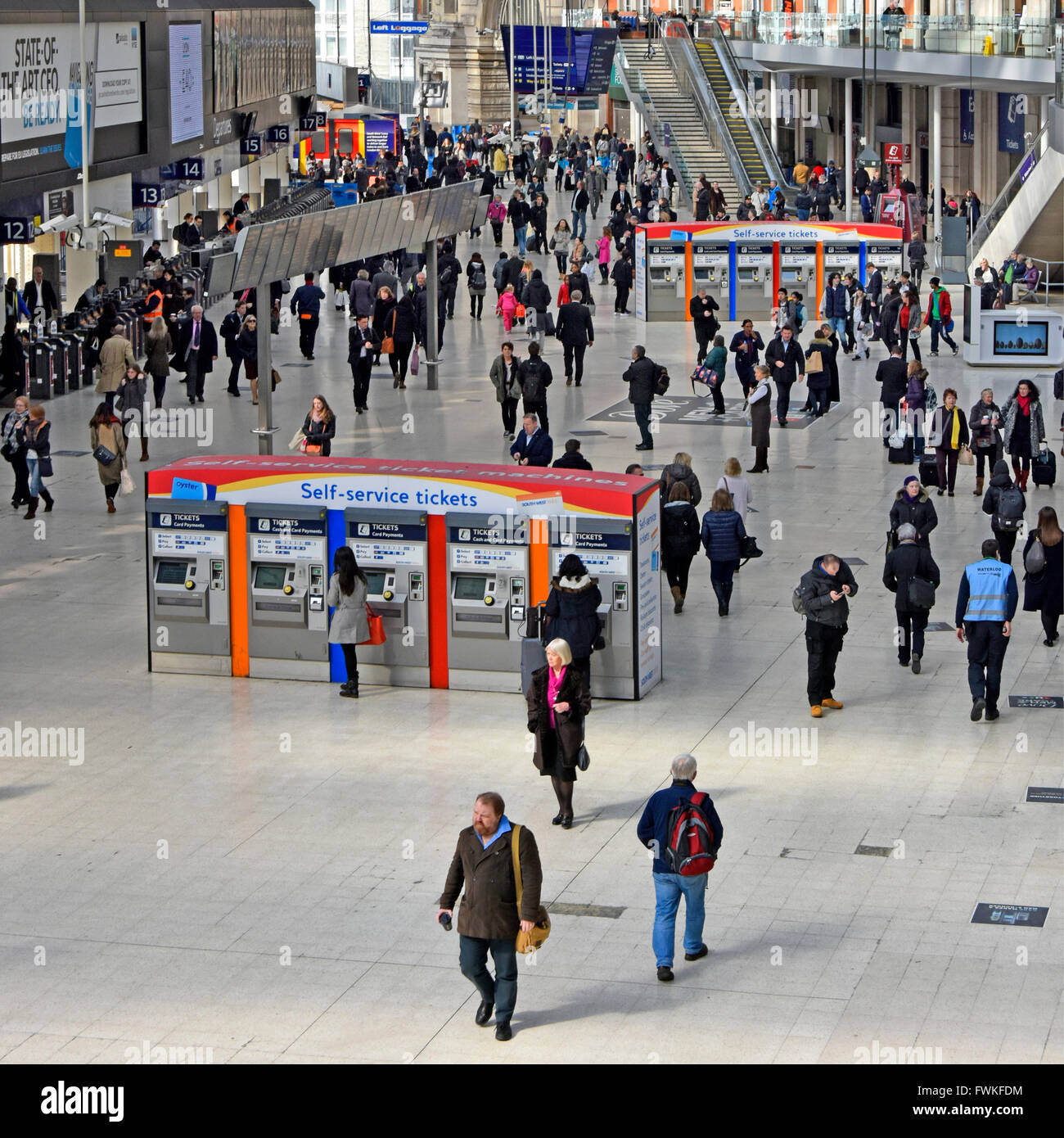 View from above looking down on commuters on London Waterloo station concourse with two rows of self service ticket - Stock Image