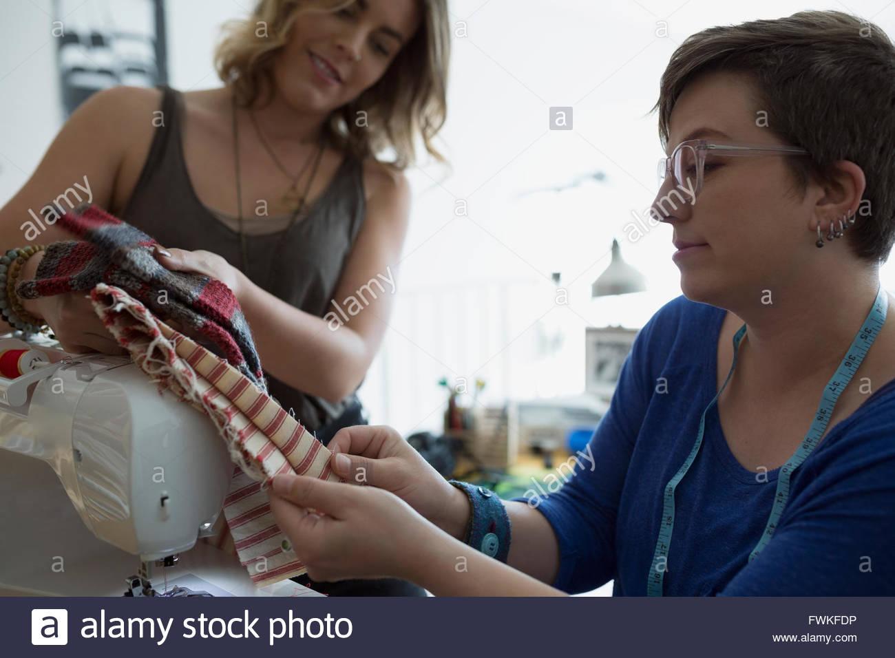 Seamstresses examining fabric at sewing machine - Stock Image