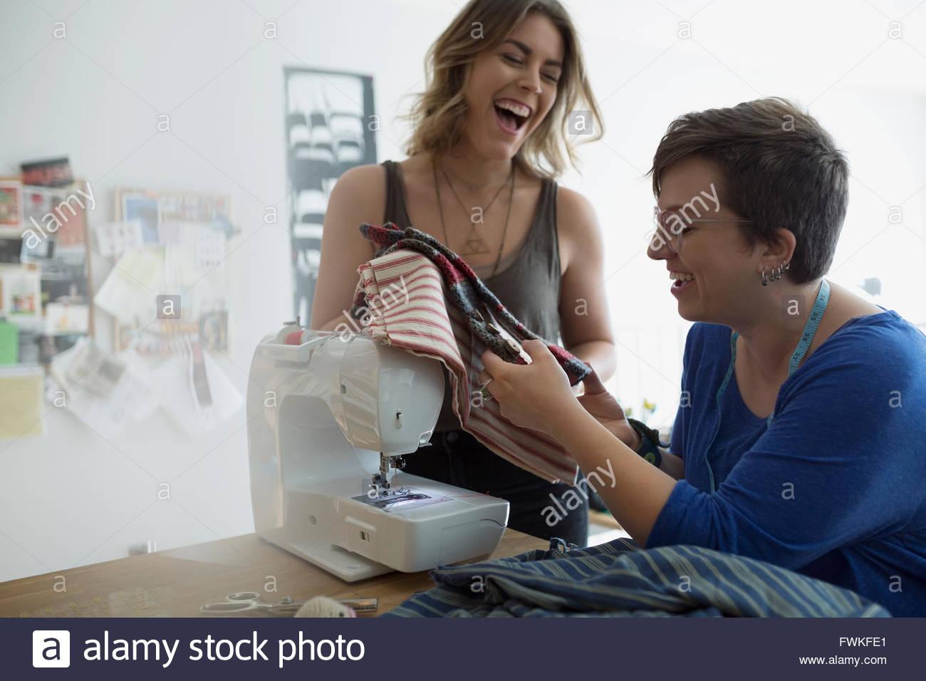 Laughing seamstresses examining fabric at sewing machine - Stock Image
