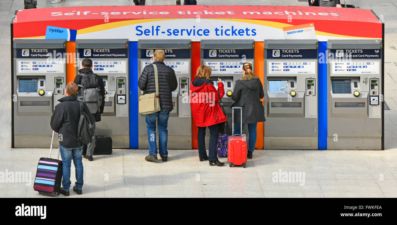 Train passengers using and waiting at self service ticket machines on the main concourse at London Waterloo mainline - Stock Image