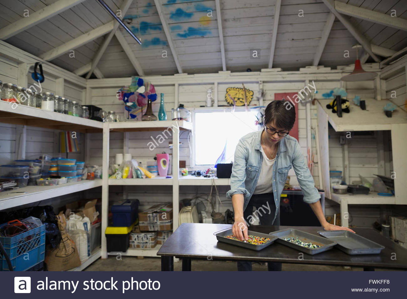 Glassblower examining loose glass pieces in workshop - Stock Image
