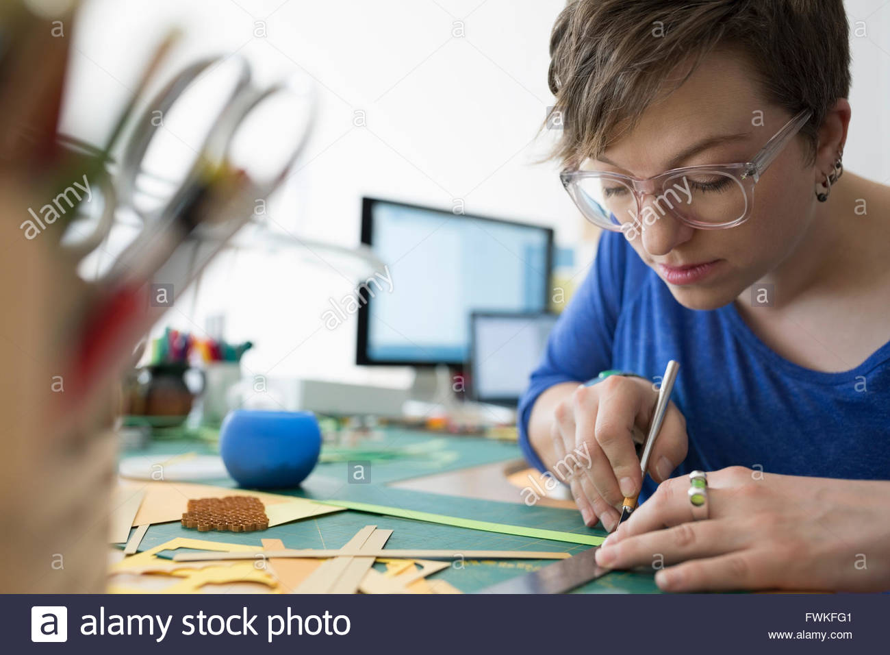 Focused craftswoman cutting pieces with ruler utility knife - Stock Image