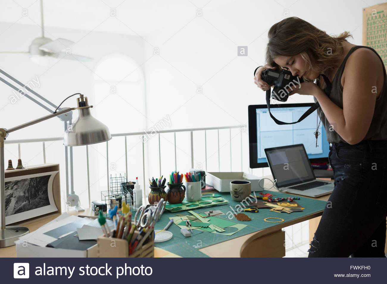 Craftswoman photographing pieces on desk in home office - Stock Image