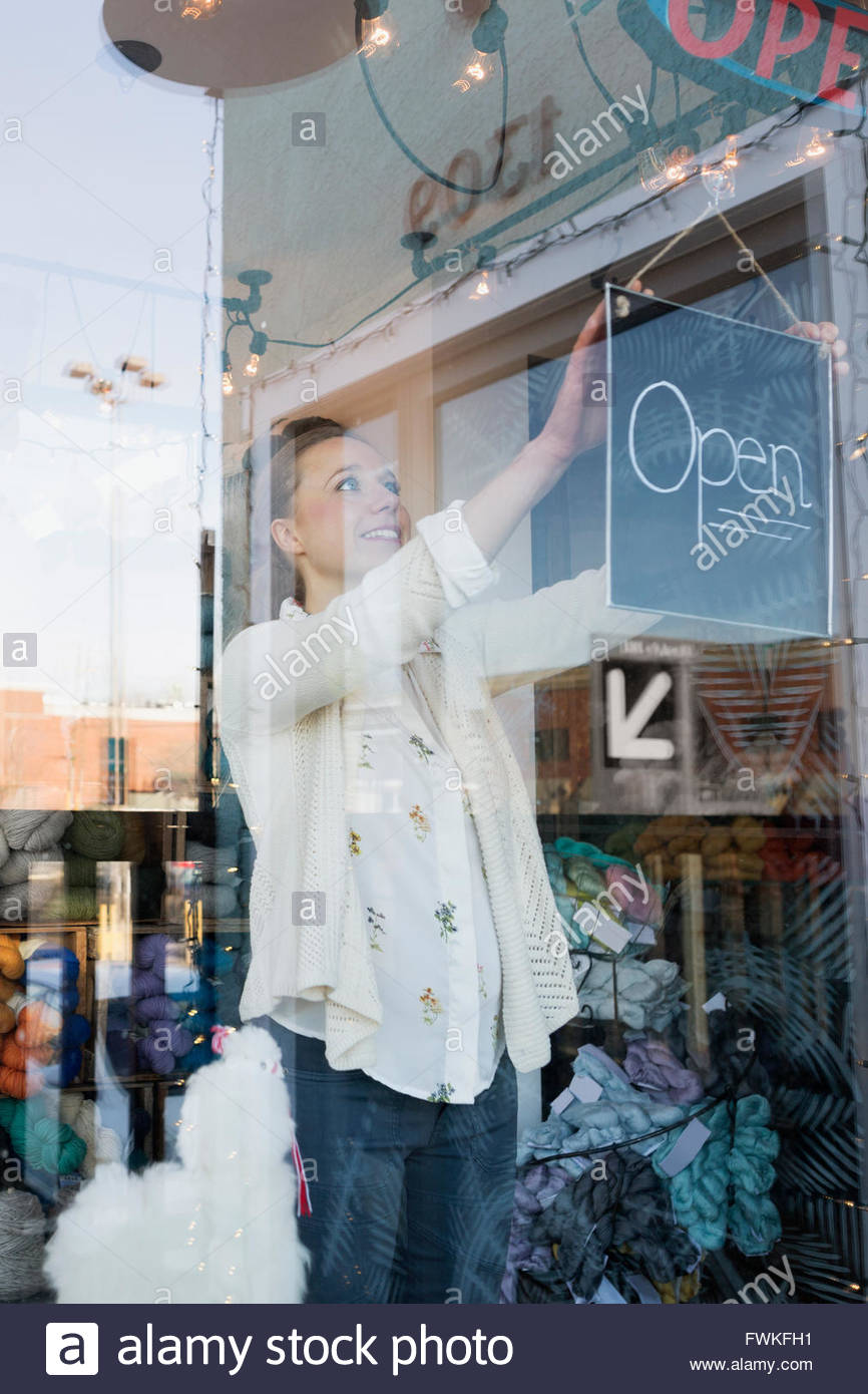 Smiling shop owner turning Open sign at window - Stock Image