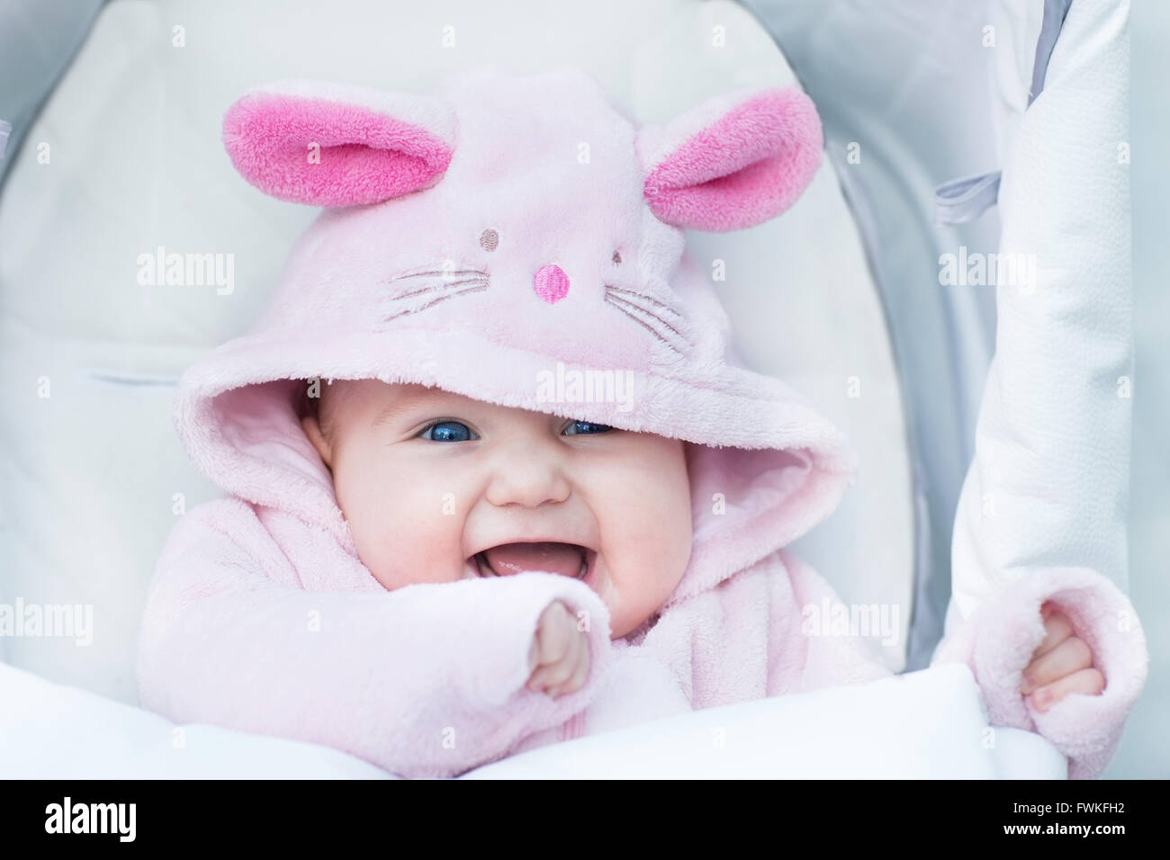 803655829 Adorable funny baby girl wearing a pink warm bunny snow suit sitting in a  white stroller