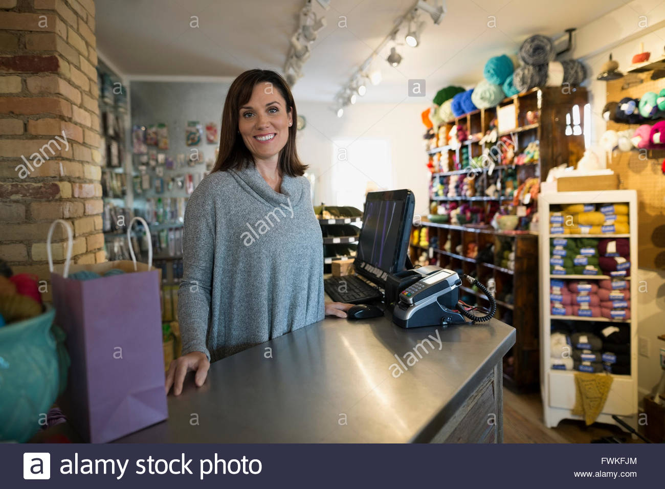 Portrait confident yarn store owner behind counter - Stock Image