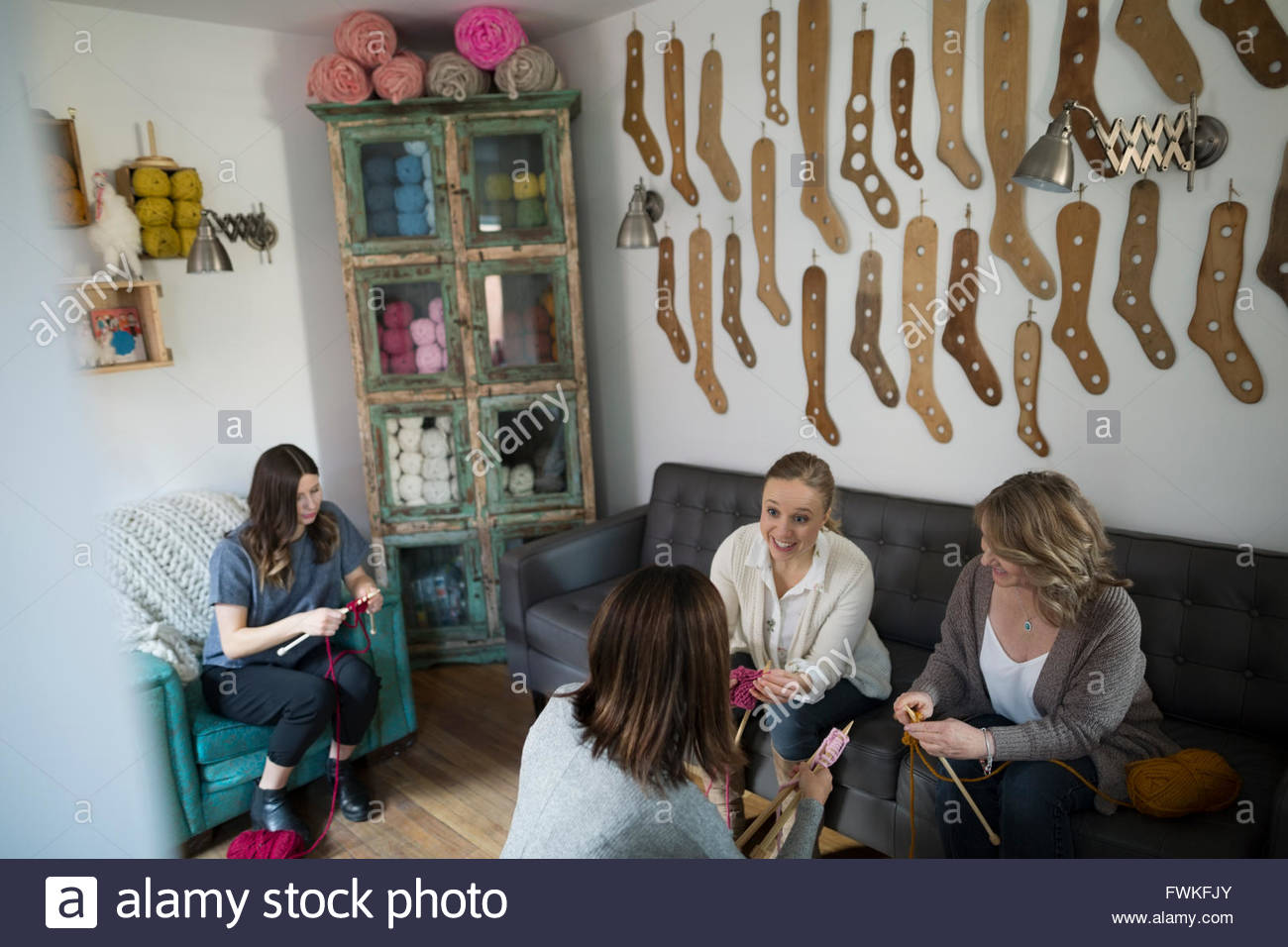 Women learning knitting at yarn store - Stock Image