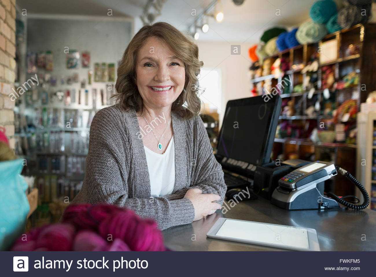 Portrait smiling yarn store owner with digital tablet - Stock Image