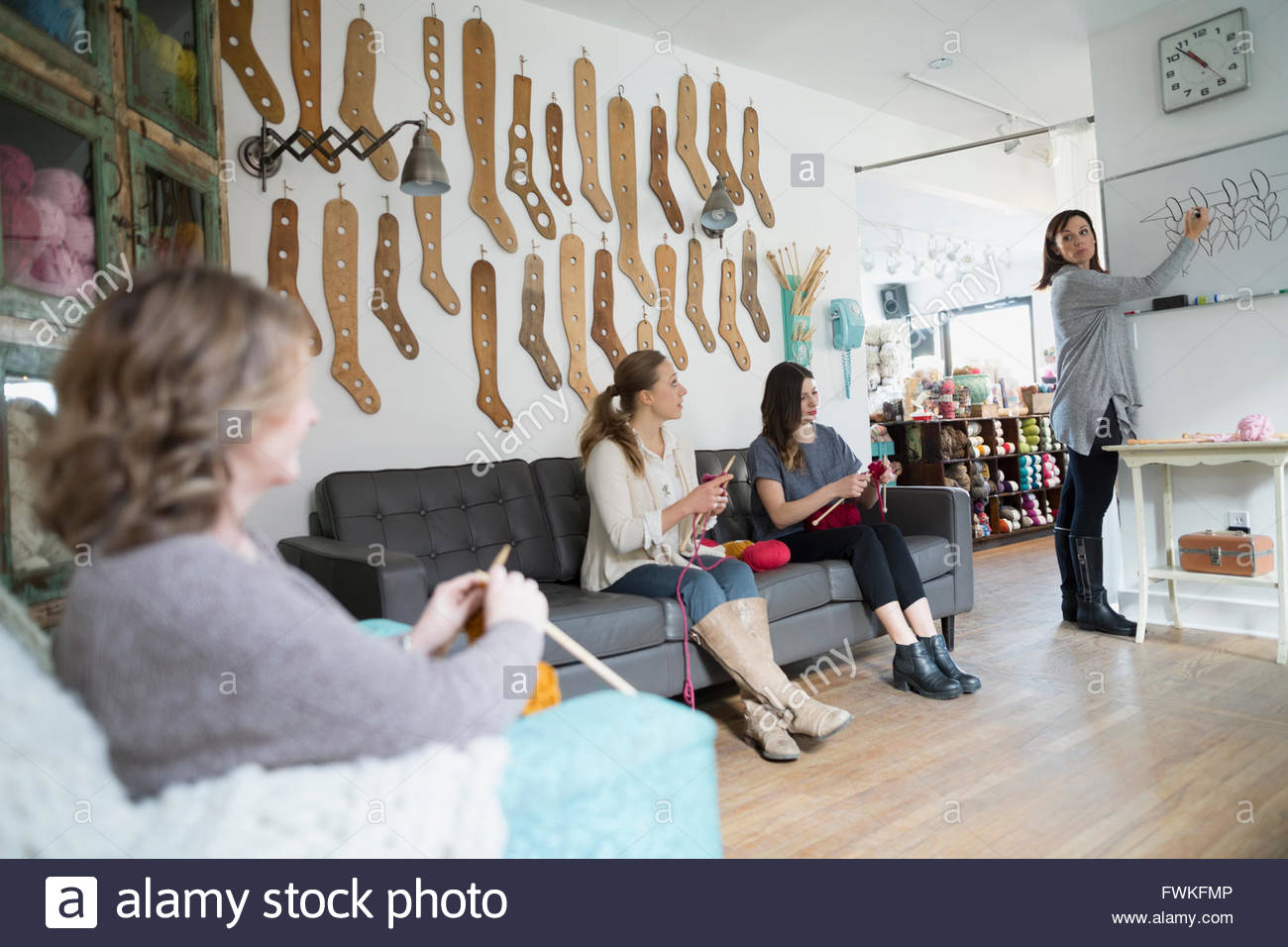 Instructor guiding knitting class at whiteboard yarn store - Stock Image