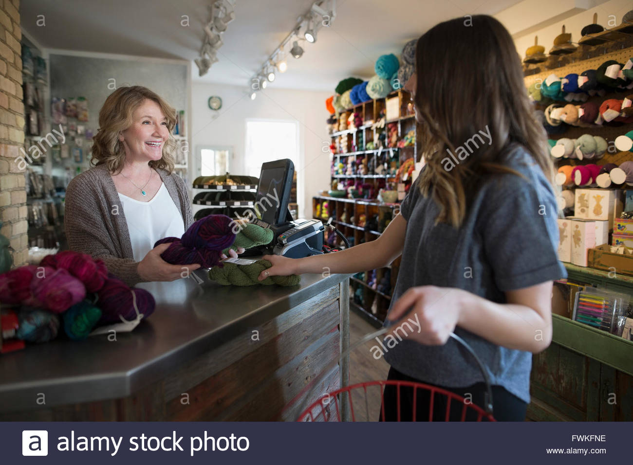 Shopper checking out at yarn store counter - Stock Image