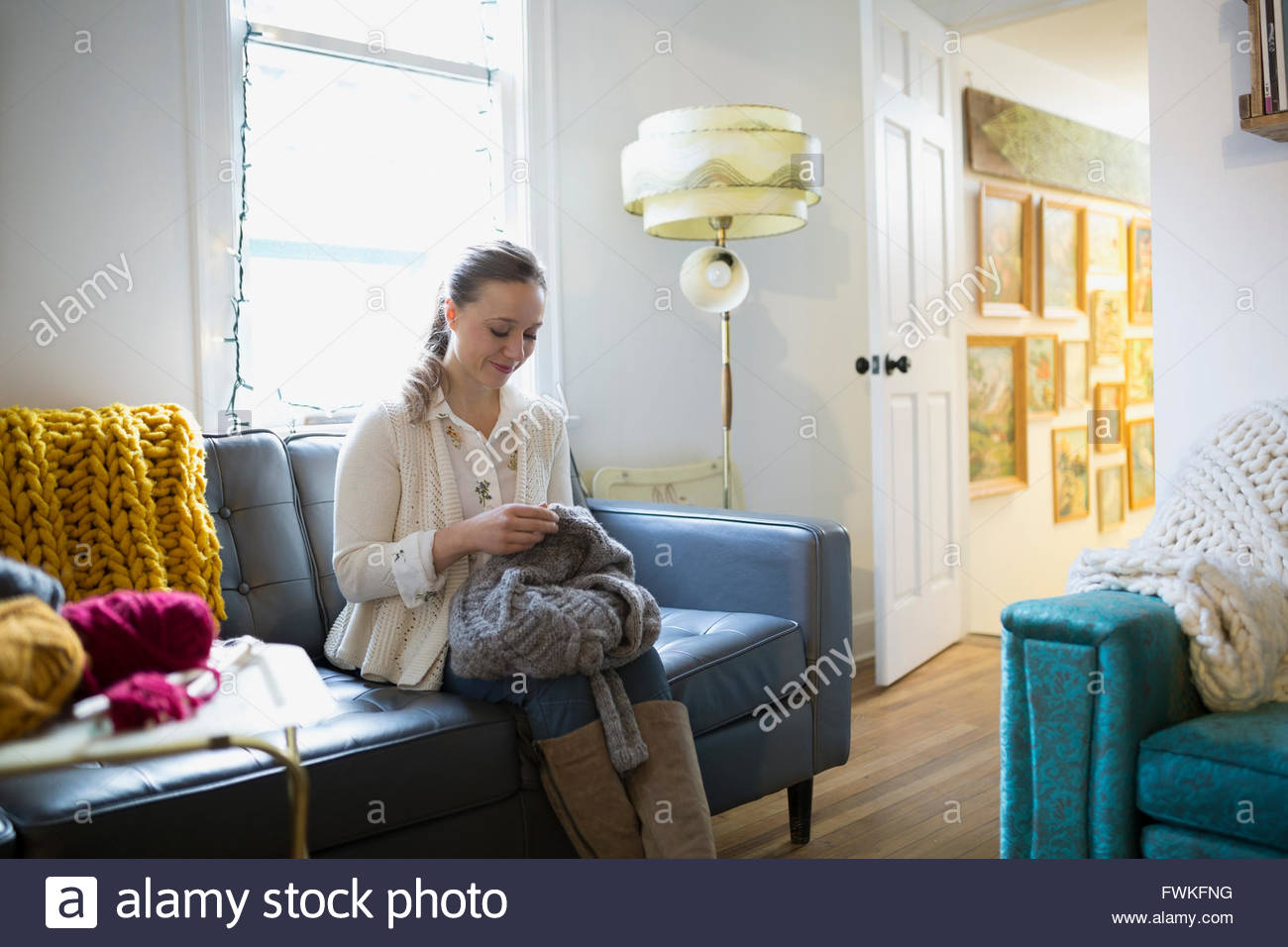 Woman knitting sweater on sofa - Stock Image