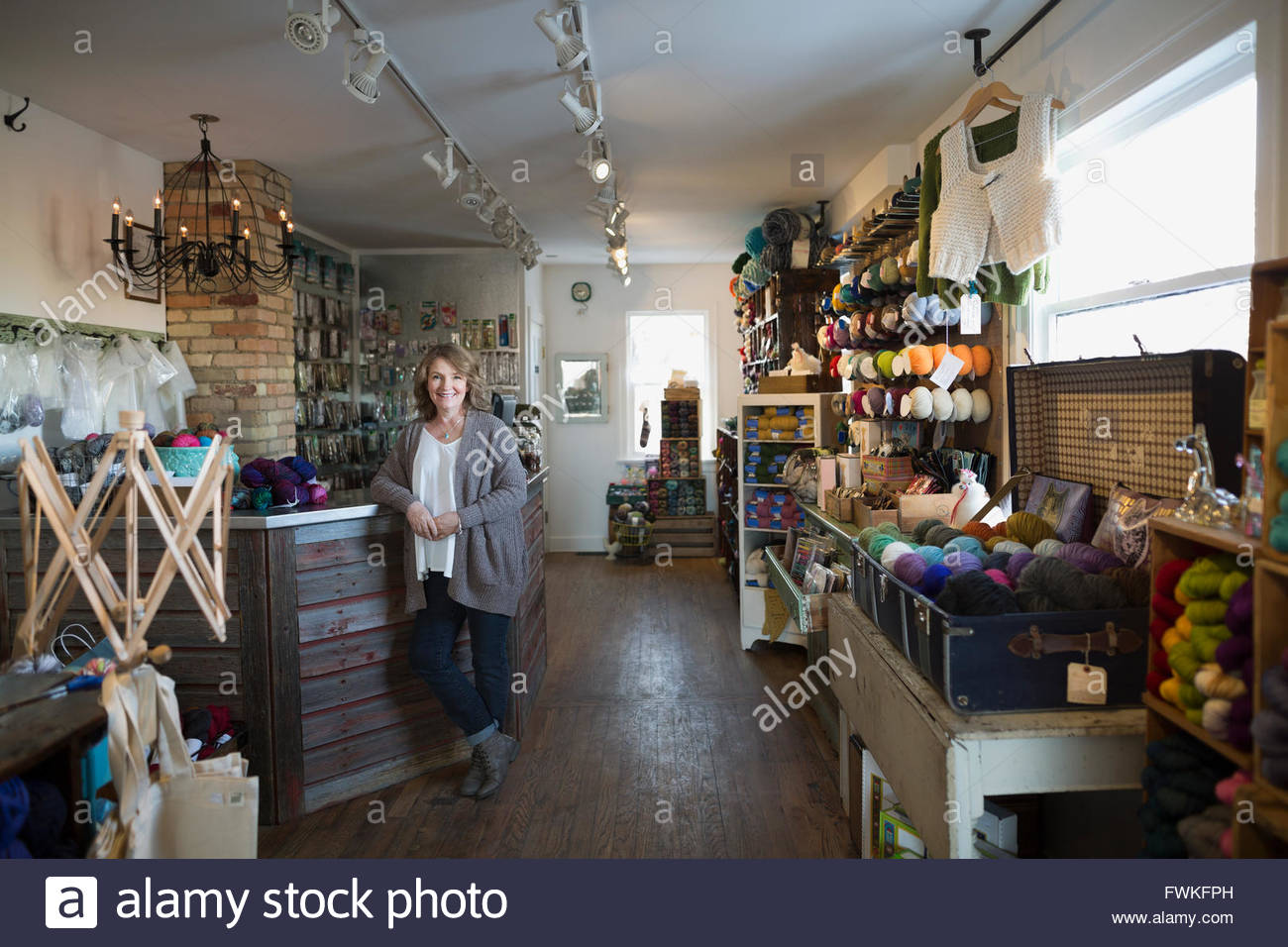 Portrait confident yarn store owner leaning on counter - Stock Image