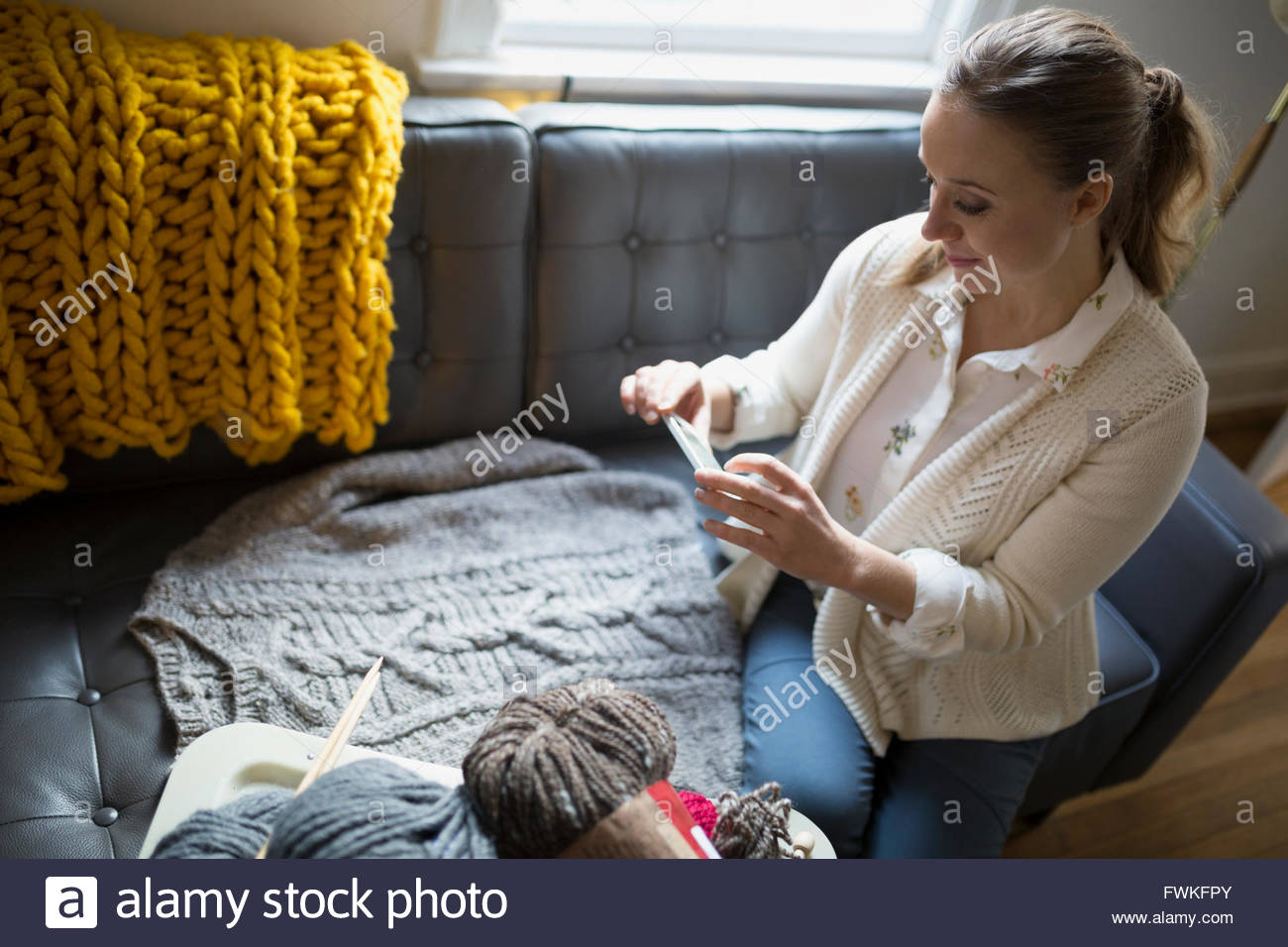 Woman photographing homemade knit sweater with camera phone - Stock Image