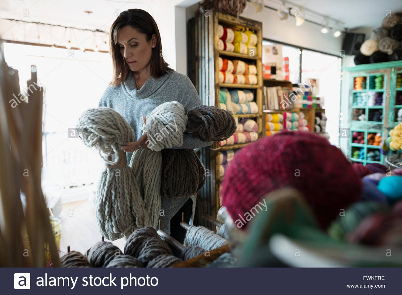 Yarn store owner arranging knit blankets - Stock Image