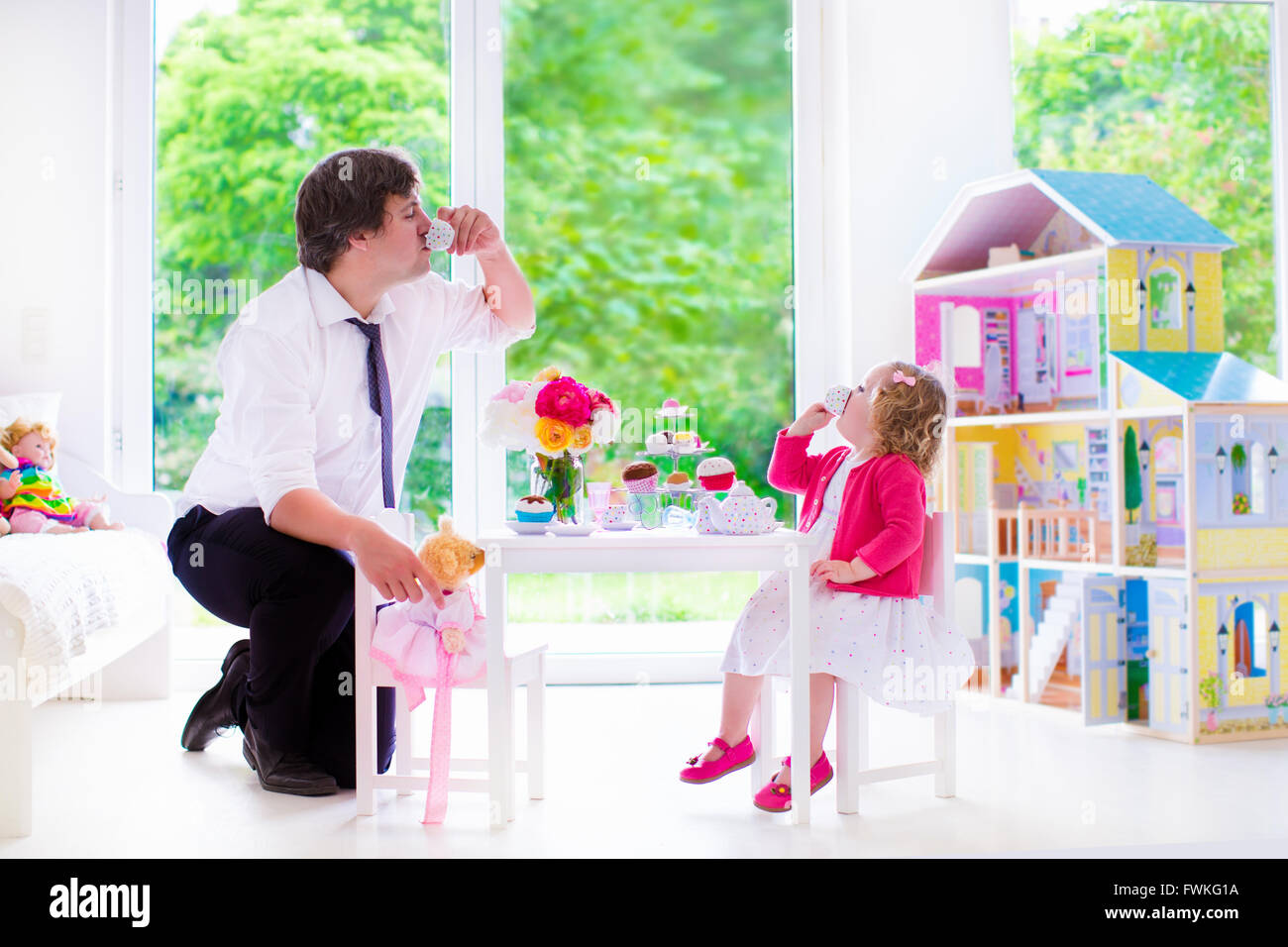 Happy family, young father and his little daughter, cute curly toddler girl wearing a dress, playing together with Stock Photo