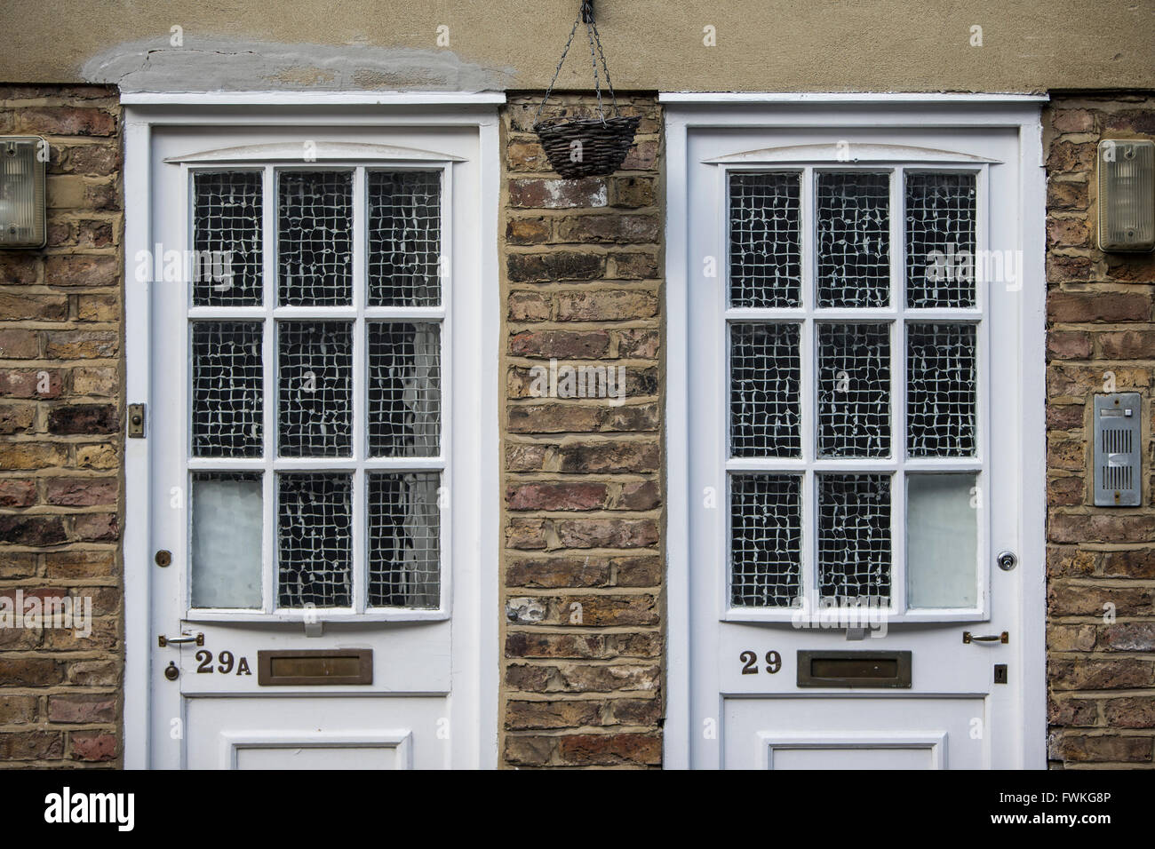 Twin doors, identical, neighbours, neighbors, white doors, old style - Stock Image