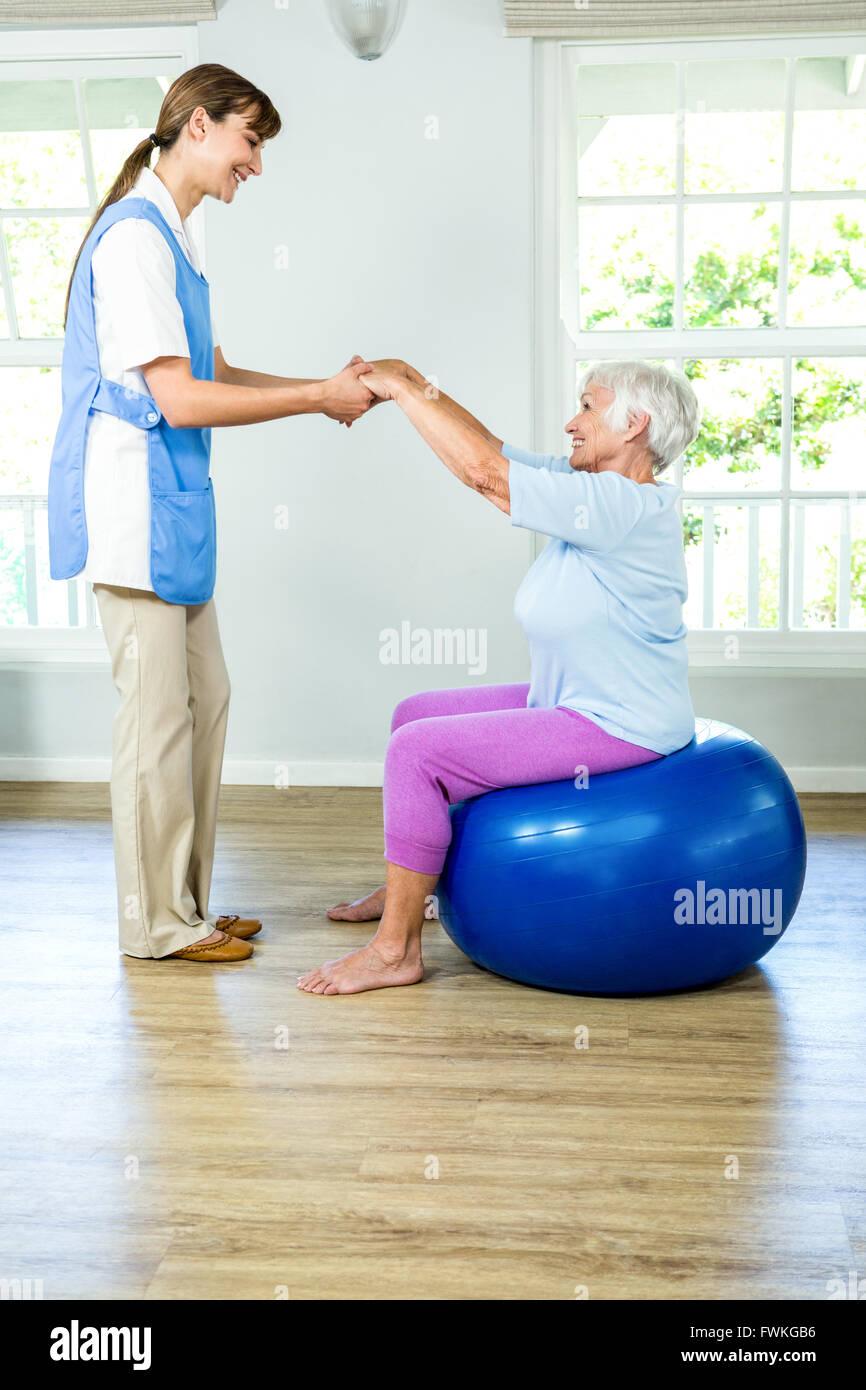Smilnig nurse assisting senior woman Stock Photo