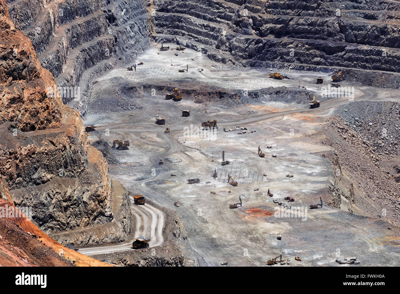 Deep down in the super pit gold mine of Kalgoorlie in Western Australia. Big exavators, trucks and other machinery - Stock Image