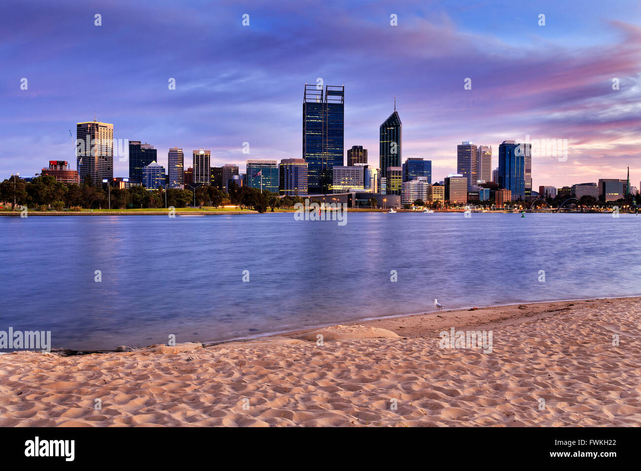 Sandy beach to Perth city CBD at sunrise when still nobody around and calm water flows in Swan river. - Stock Image