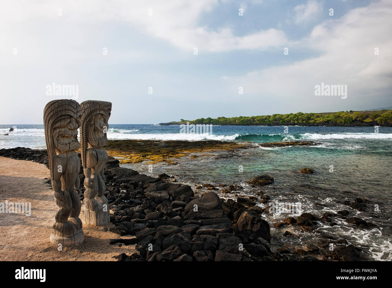 Fierce Ki'i statues stand guard overlooking Honaunau Bay at The Place of Refuge on the Big Island of Hawaii. - Stock Image