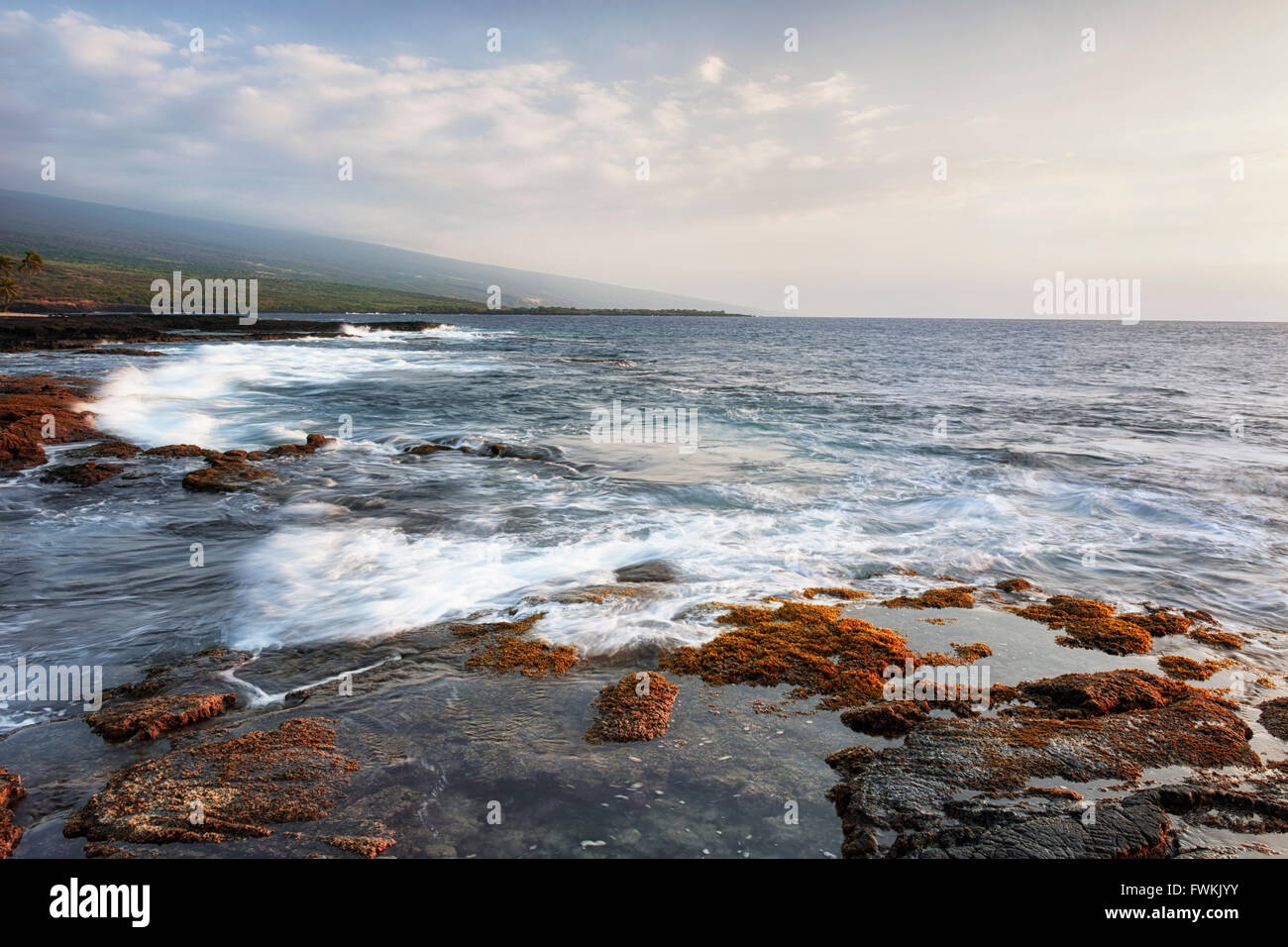 Evening surf pours over the tide pools at The Place of Refuge National Historical Park on the Big Island of Hawaii. - Stock Image
