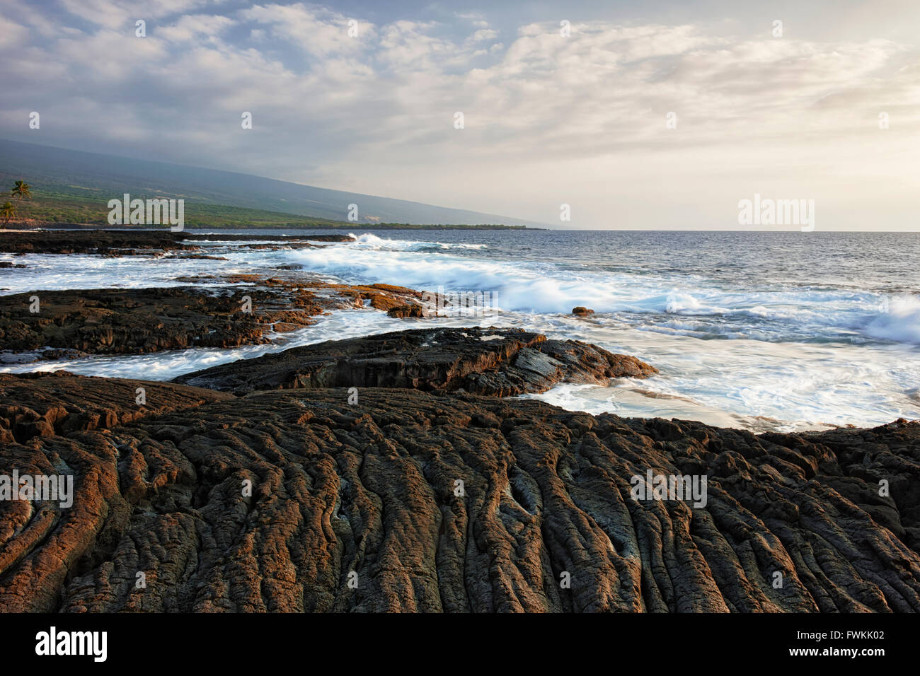 Pahoehoe lava flow meets the Pacific Ocean at The Place of Refuge National Historical Park on the Big Island of - Stock Image