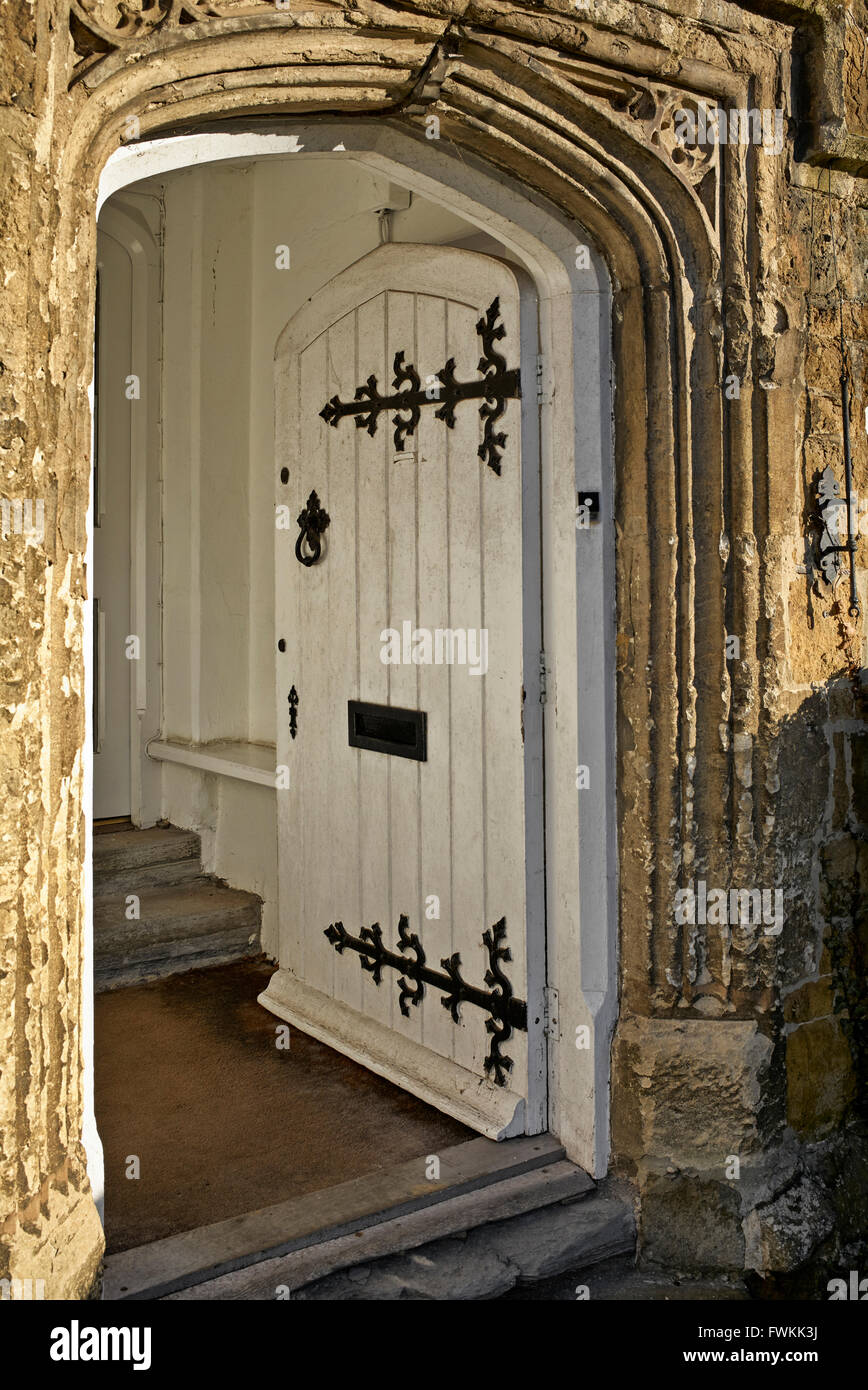 Ancient stone arched entrance with ornate hinged door. Banbury historic town England UK - Stock Image