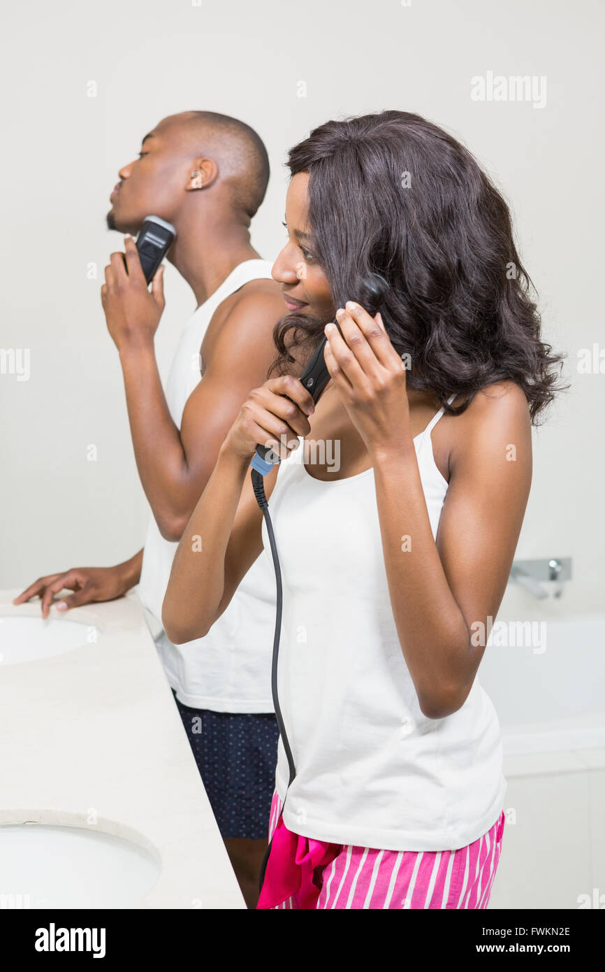 Young man shaving and young woman straightening hair - Stock Image