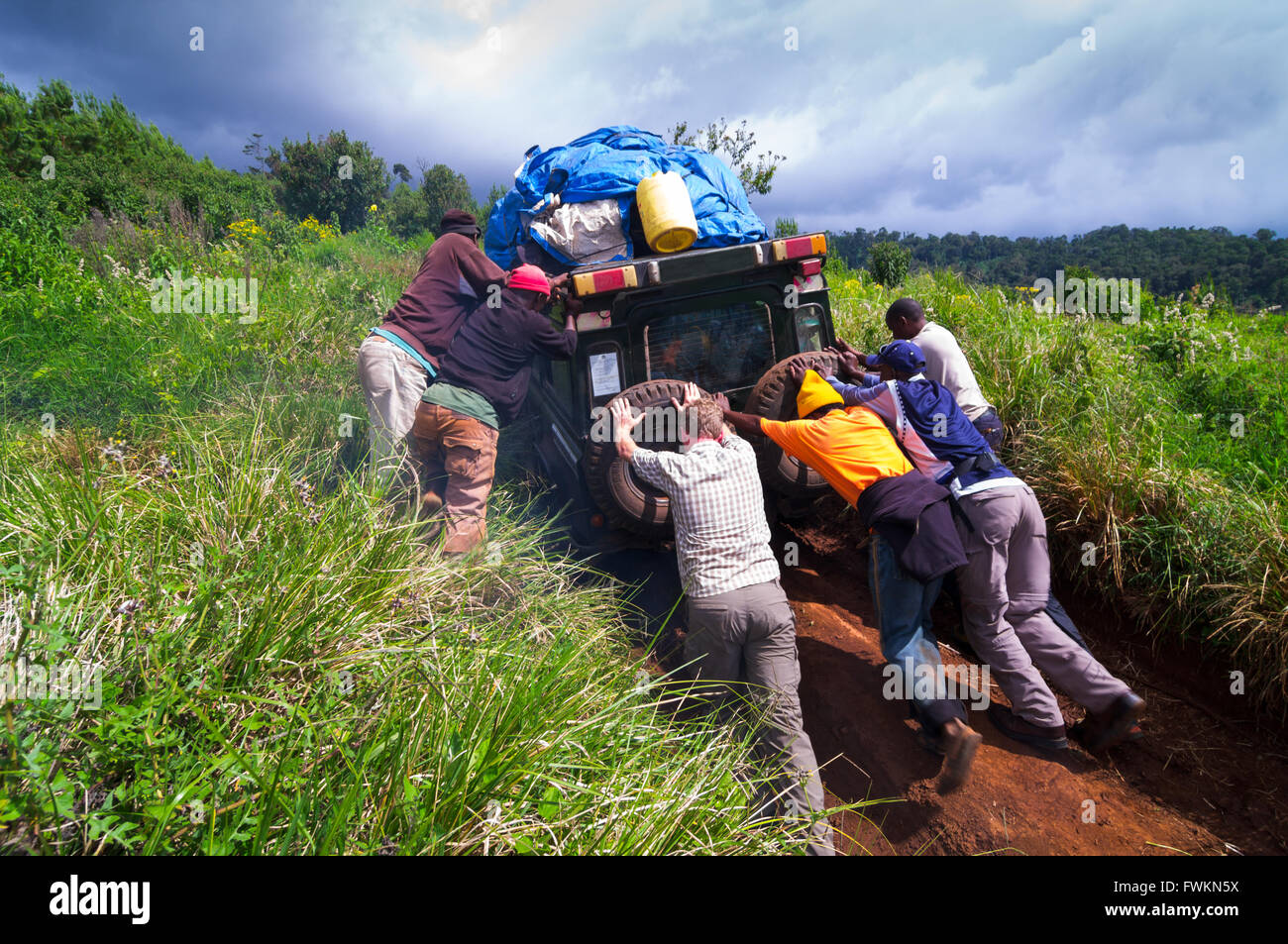 Men trying to push 4WD vehicle up steep and slippery road to beginning of Lemosho Route, Mt Kilimanjaro, Tanzania, - Stock Image