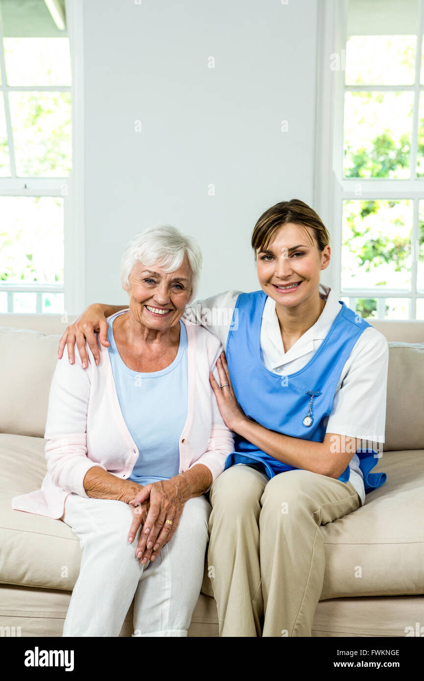 Portrait of happy nurse with senior woman at home - Stock Image