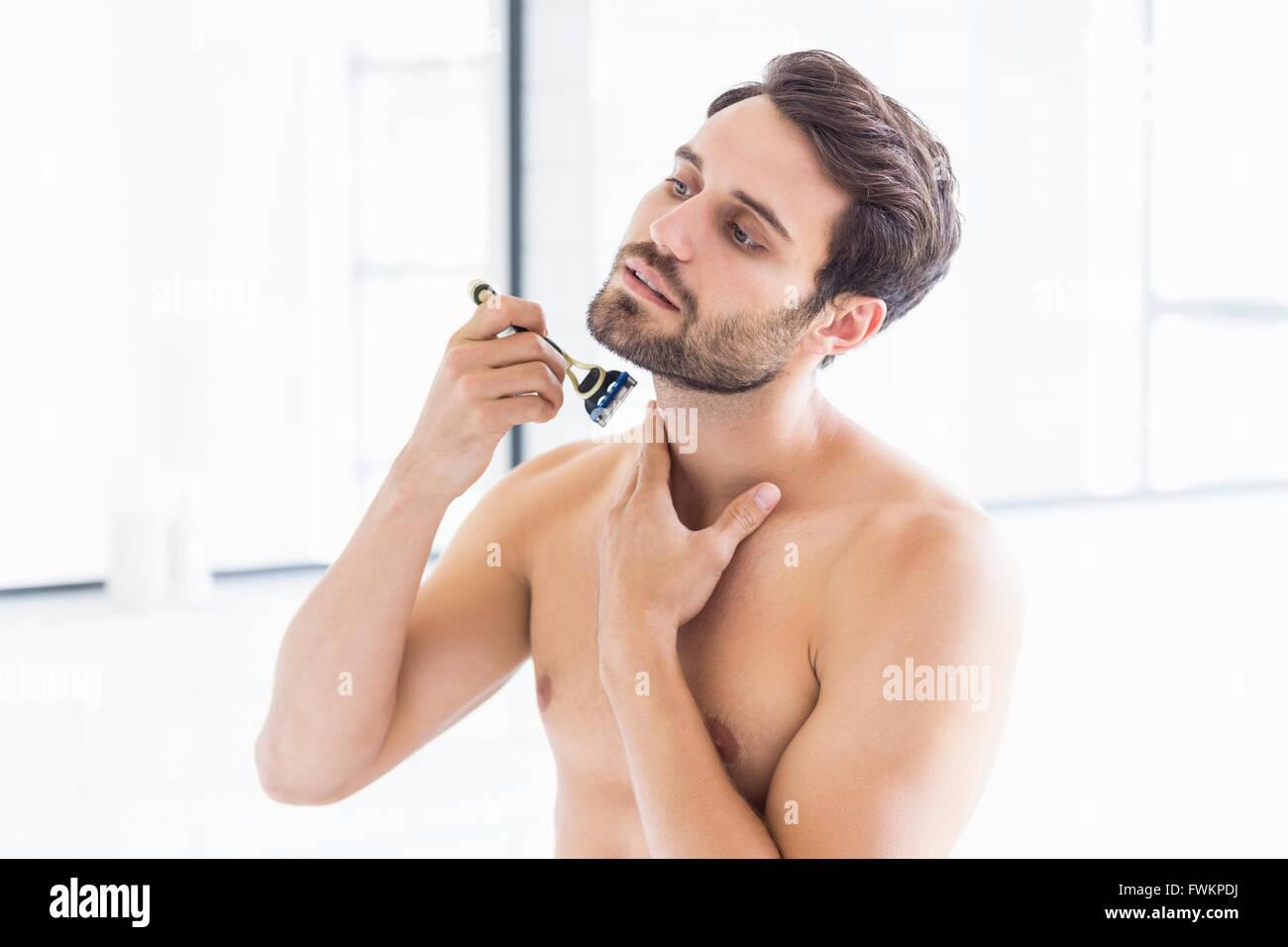 Man shaving in the bathroom - Stock Image