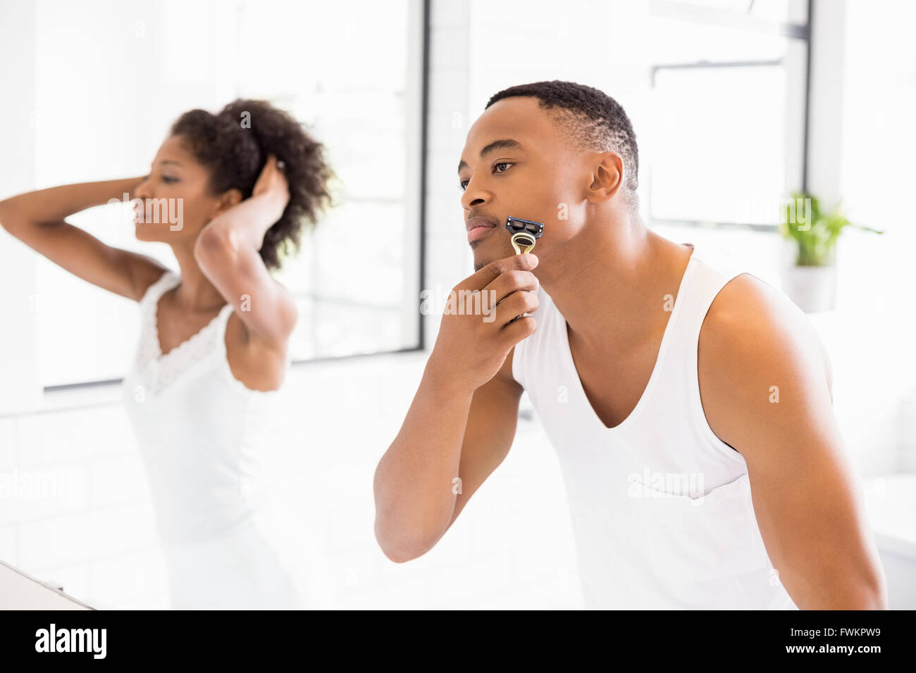 Man shaving with razor in bathroom - Stock Image