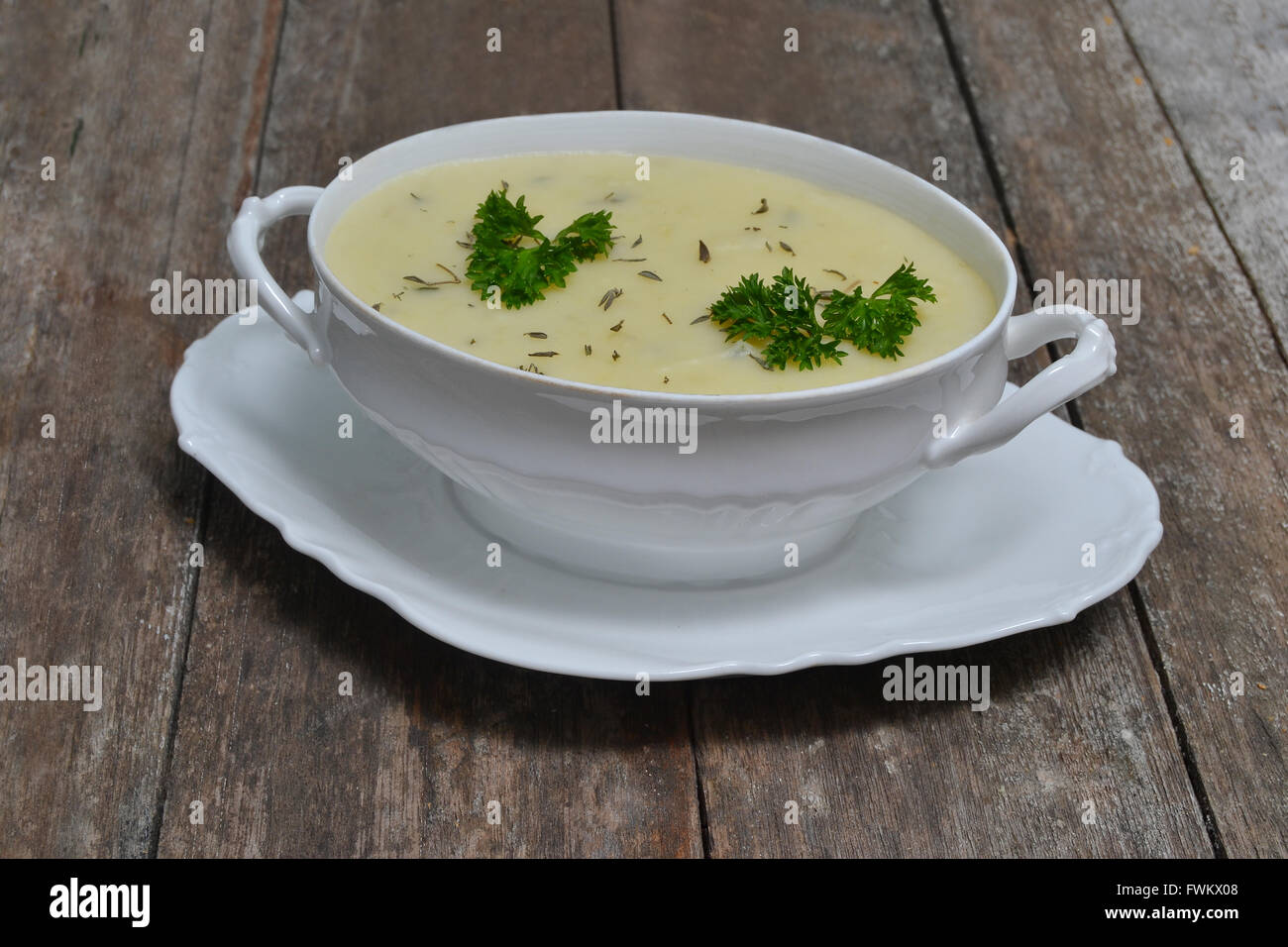 mashed potato garnish with parsley in a bowl on rustic wood - Stock Image