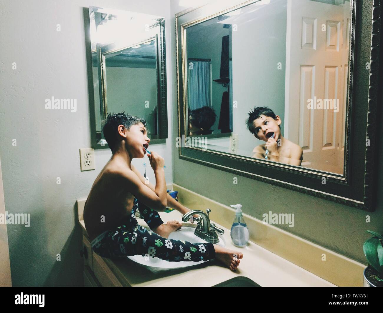 Cute Shirtless Boy Brushing Teeth In Front Of Mirror While Sitting On Sink - Stock Image
