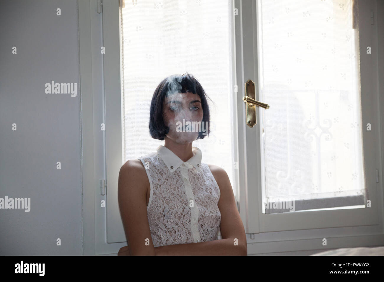 Portrait Of Woman Smoking Against Window At Home - Stock Image
