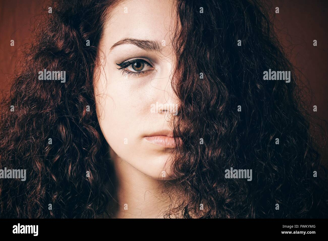 Close-Up Portrait Of Woman With Curly Hair - Stock Image