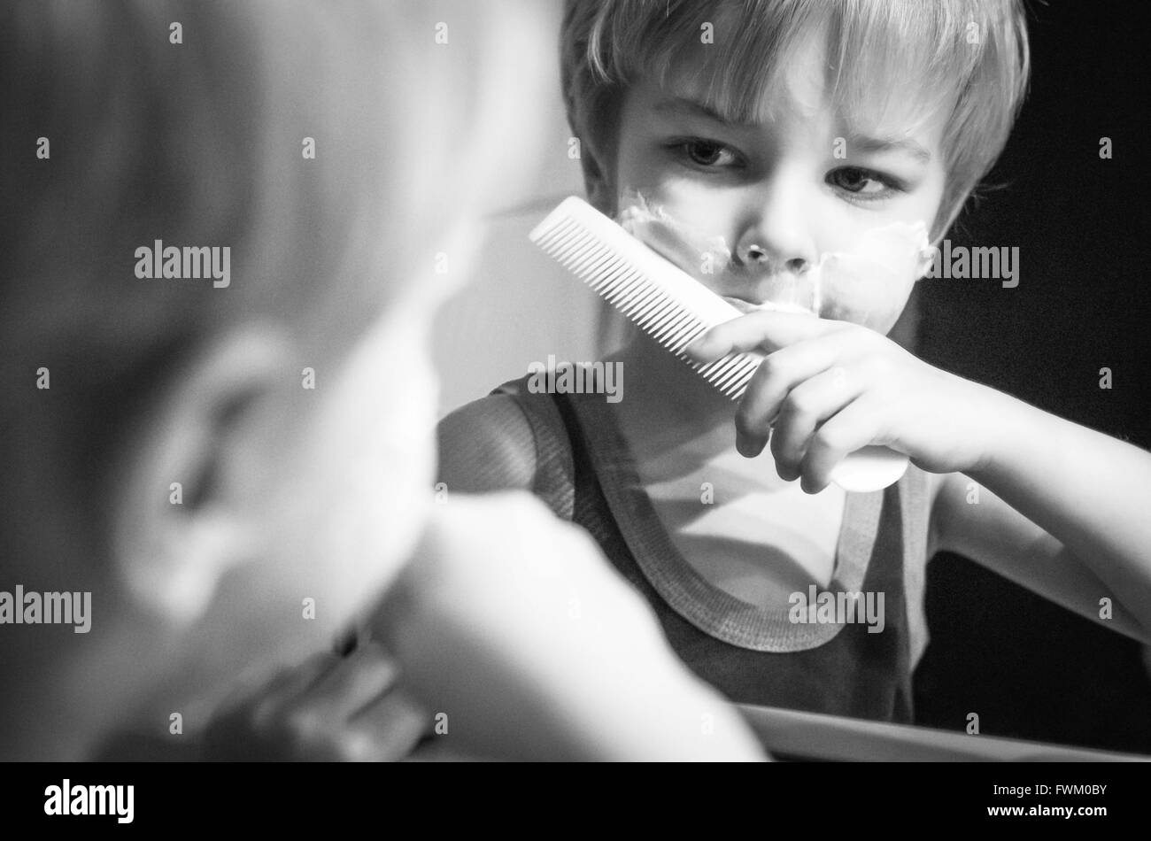 Reflection Of Boy Holding Comb On Mirror In Bathroom - Stock Image