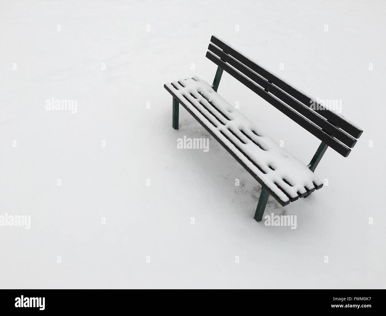 High Angle View Of Frozen Park Bench During Winter - Stock Image