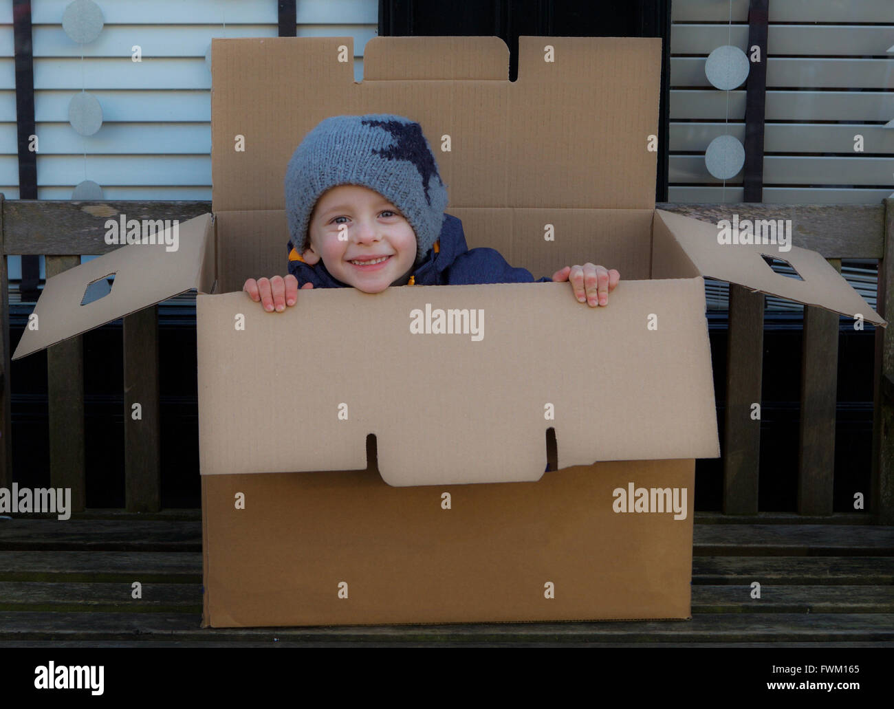Portrait Of Playful Boy On Box - Stock Image