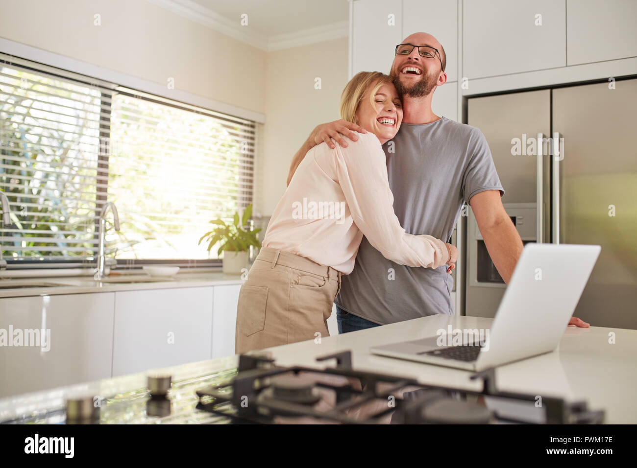 Portrait of happy woman embracing her husband in kitchen. Loving couple with laptop on  kitchen counter at home. - Stock Image