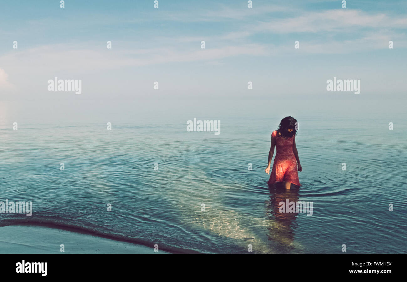 Woman Standing In Sea Against Sky - Stock Image