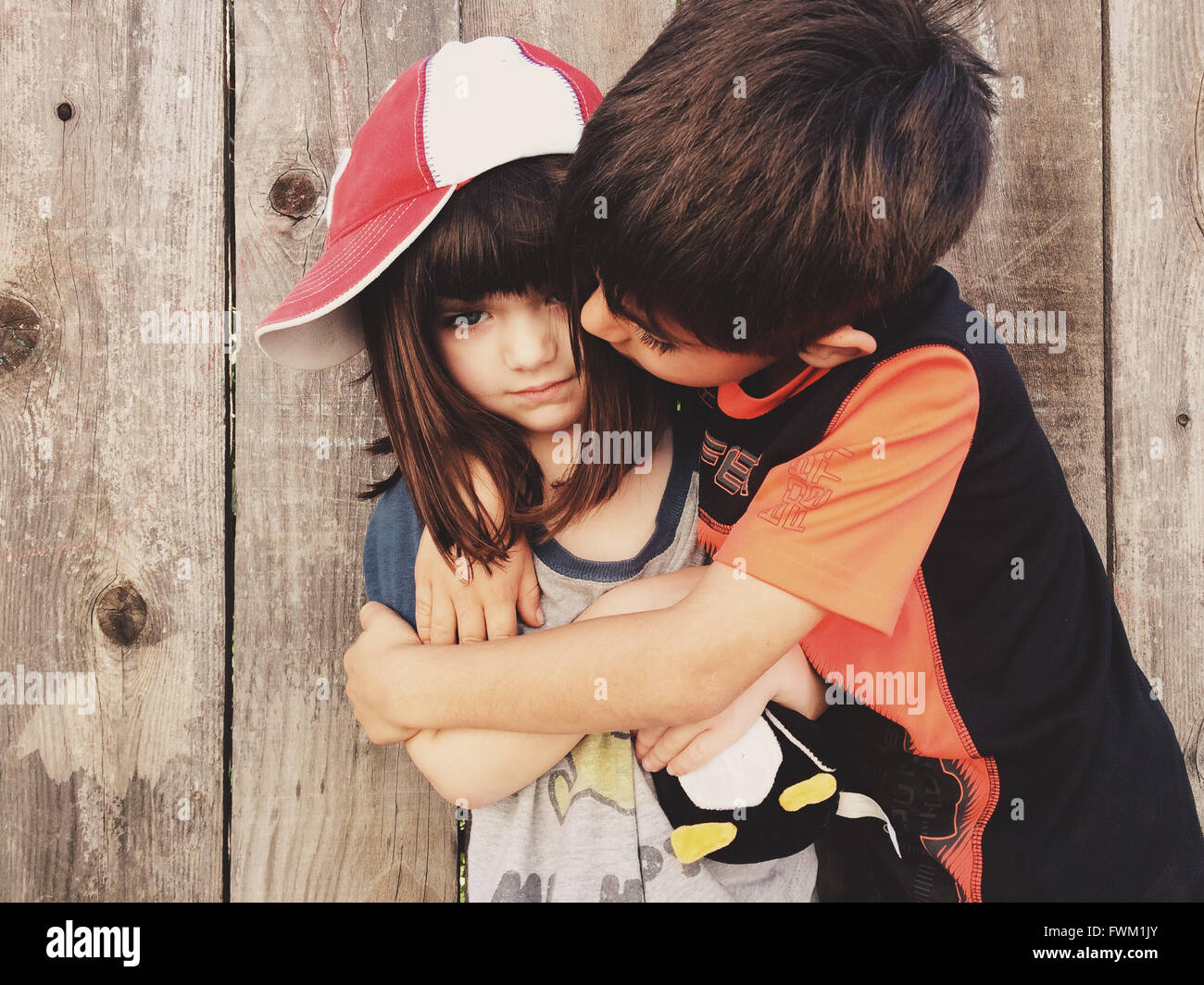 Cute Sibling Embracing Against Wooden Wall - Stock Image