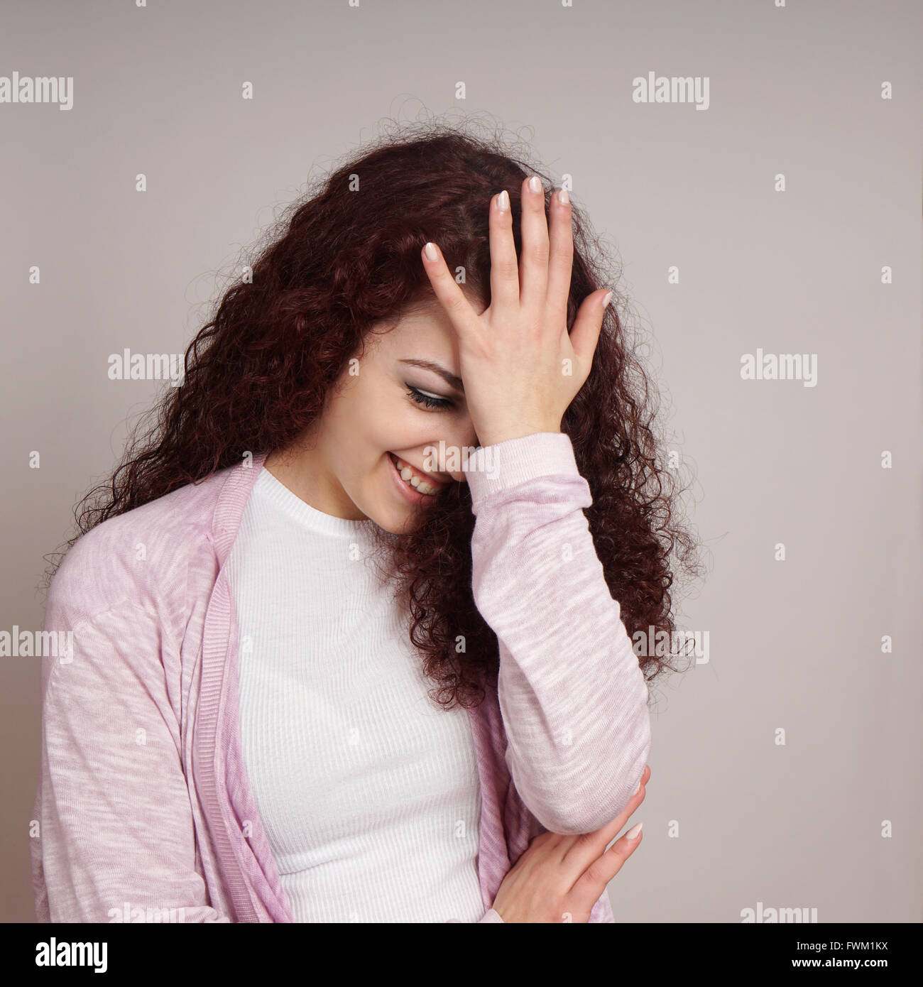 Smiling Young Woman Standing Against Wall - Stock Image
