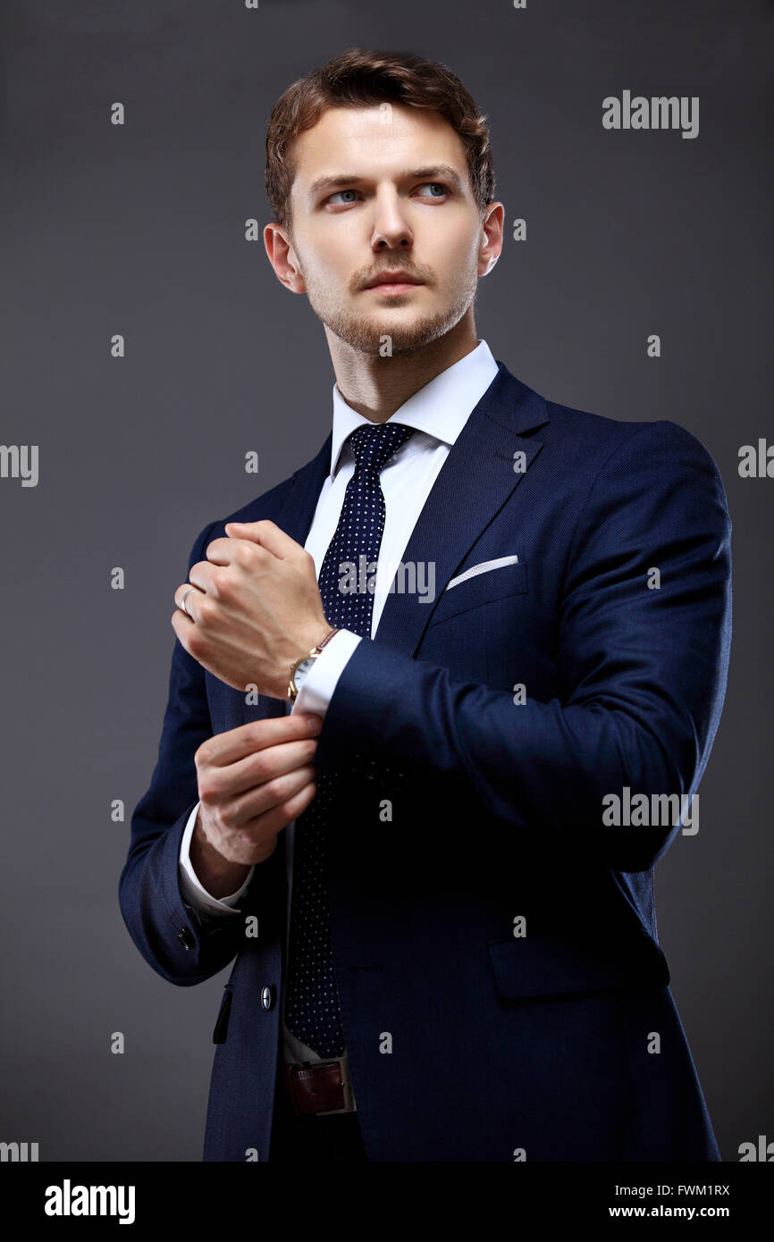 Cool businessman standing on grey - Stock Image