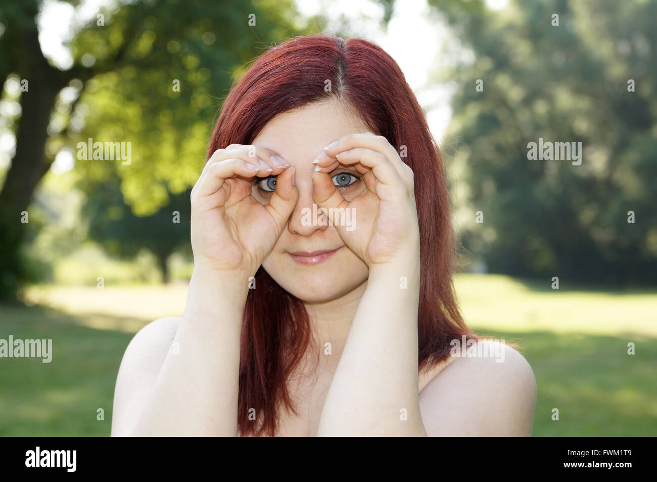 Portrait Of Young Woman Peering Through Hands In Park - Stock Image