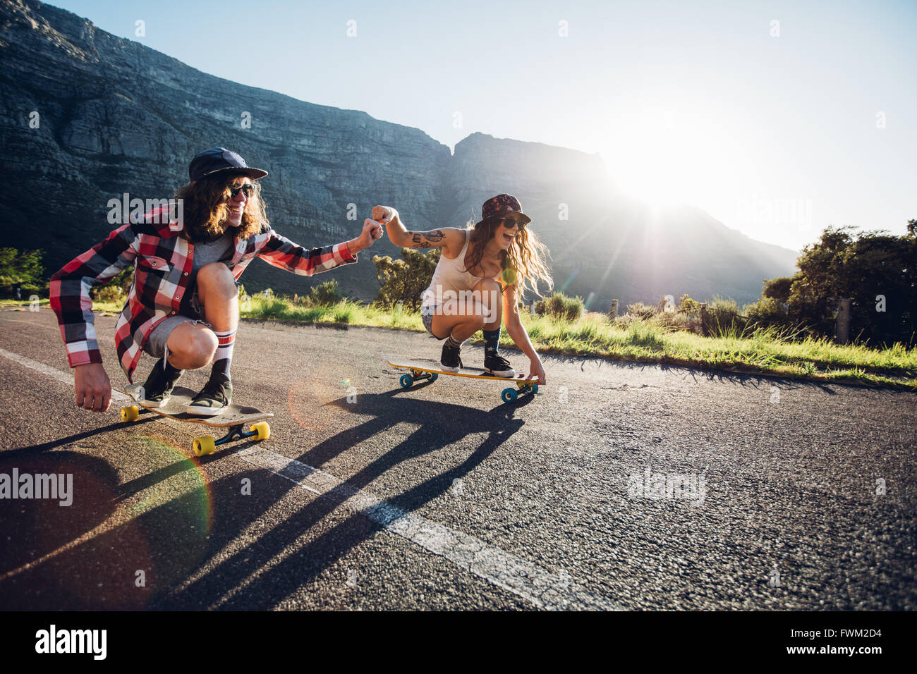 Happy young couple having fun with skateboard on the road. Young man and woman skating together on a sunny day. Stock Photo