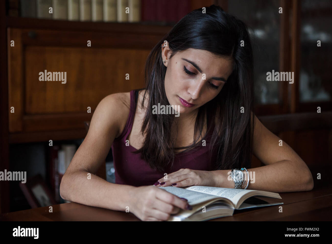 Concentrated Young Woman Reading Book At Desk - Stock Image