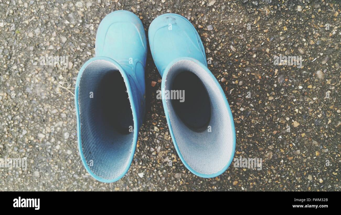 Directly Above Shot Of Rubber Boots On Street - Stock Image