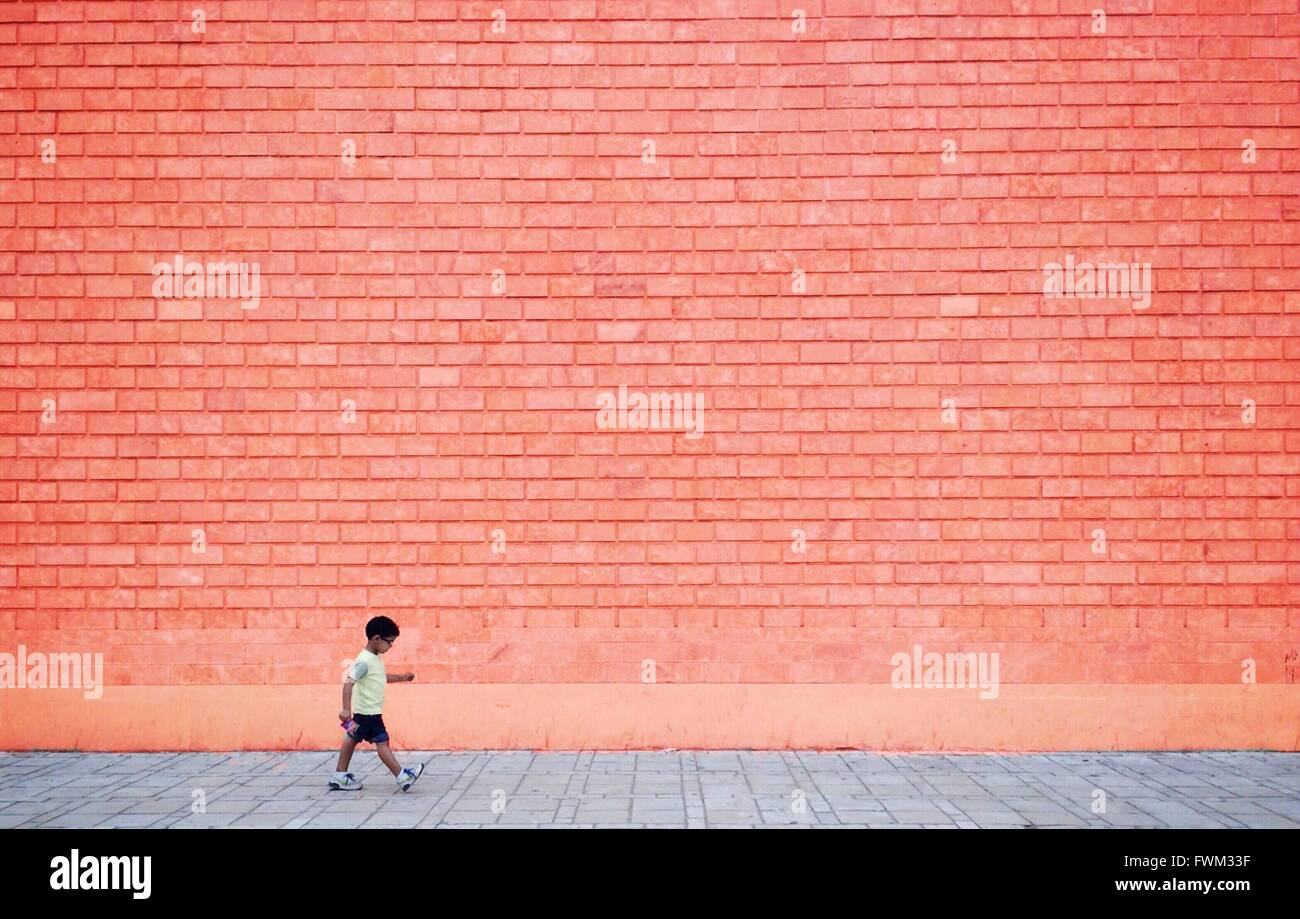 Full Length Of Boy Walking On Sidewalk Against Wall - Stock Image