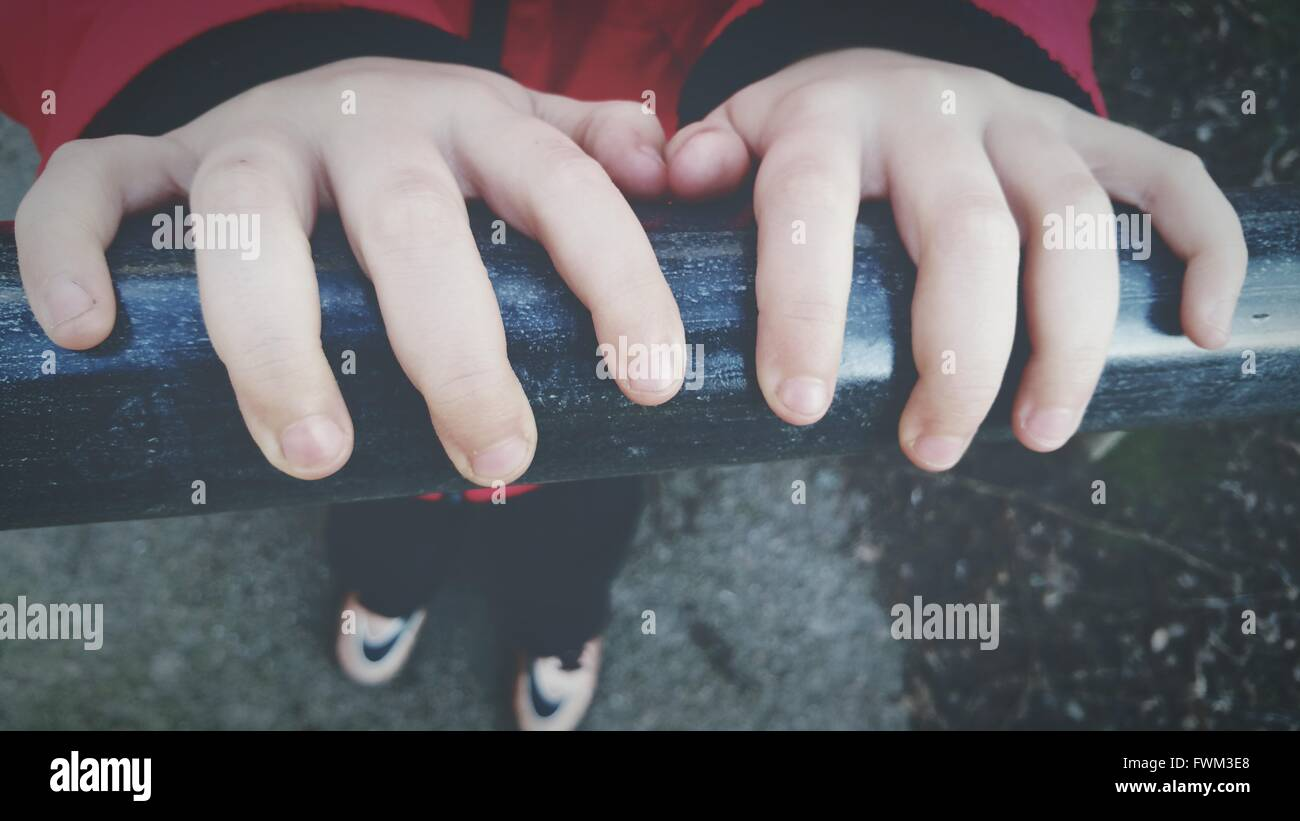 Close-Up Of Boy Hands On Railing - Stock Image